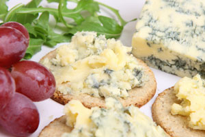 stilton cheese on crackers, with red grapes